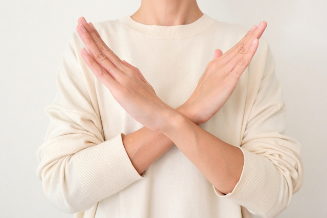 体の前でばつをする女性