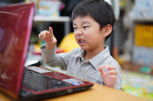 パソコンの前で怒ってる男の子